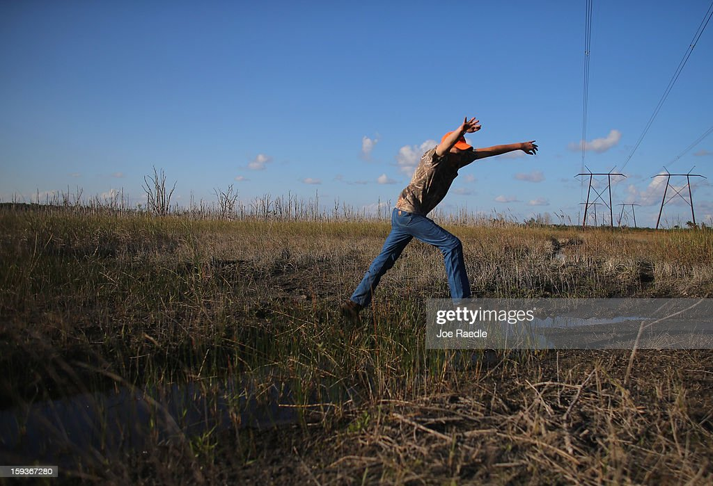 Kyle Storch jumps over a patch of water as he hunts for python's in the Florida Everglades on the first day of the 2013 Python Challenge on January 12, 2013 in Miami, Florida.The Florida Fish and Wildlife Conservation Commission and its partners launched the month long 2013 Python Challenge to harvest Burmese pythons in the Florida Everglades, a species that is not native to Florida.The contest features prizes of $1,000 for catching the longest snake and $1,500 for catching the most.