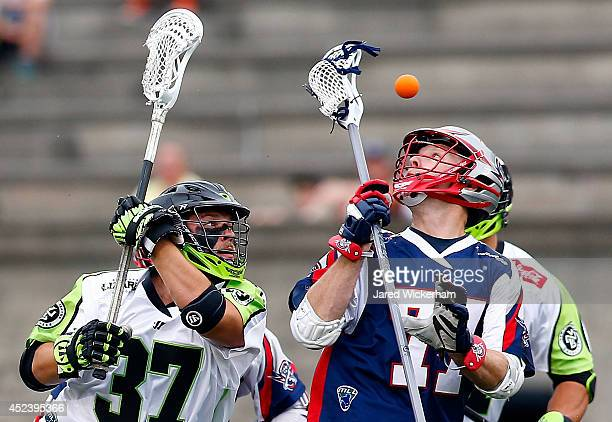 Kyle Sweeney of the Boston Cannons and Jerry Ragonese of the New York Lizards reach for a loose ball in the first half during the game at Harvard...