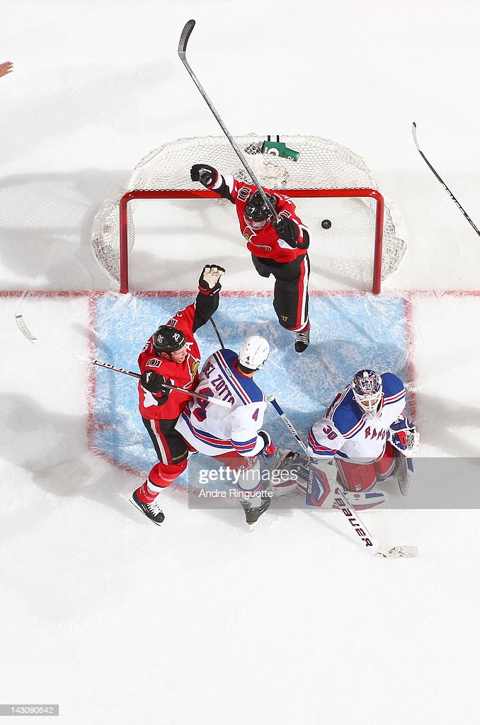 Kyle Turris and Chris Neil of the Ottawa Senators celebrate a second period goal against Michael Del Zotto and Henrik Lundqvist of the New York...