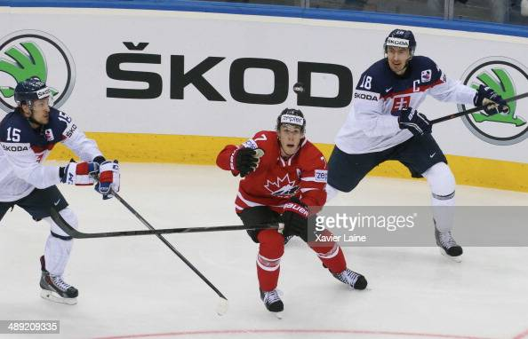 Kyle Turris of Canada catch the puck over Marek Hrivik and Miroslav Satan of Slovakia during the 2014 IIHF World Championship between Canada and...