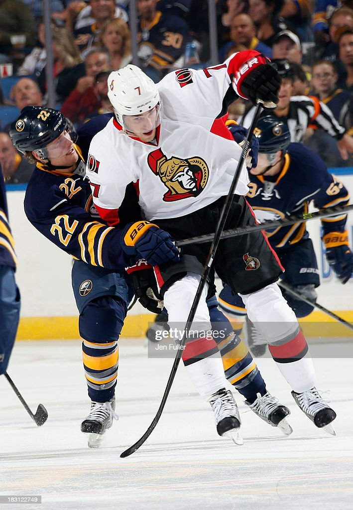 Kyle Turris #7 of the Ottawa Senators and Johan Larsson #22 of the Buffalo Sabres get tangled up while battling for the puck at First Niagara Center on October 4, 2013 in Buffalo, New York.