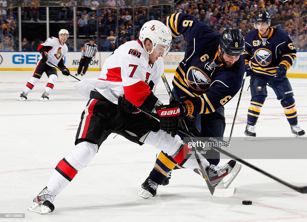 Kyle Turris #7 of the Ottawa Senators and Mike Weber #6 of the Buffalo Sabres battle for control of the puck at First Niagara Center on October 4, 2013 in Buffalo, New York. Ottawa defeated Buffalo 1-0.