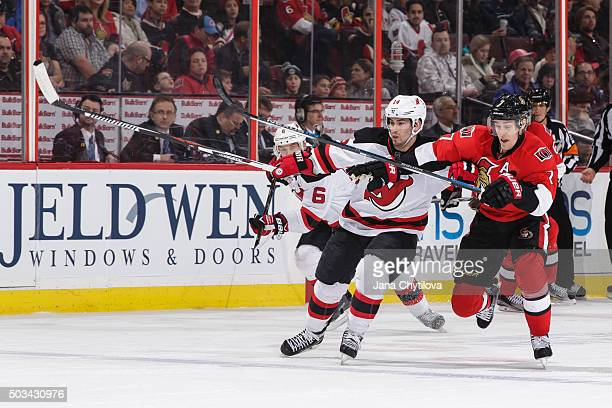 Kyle Turris of the Ottawa Senators battles for position against Adam Henrique of the New Jersey Devils at Canadian Tire Centre on December 30 2015 in...