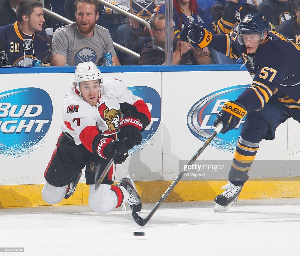Kyle Turris #7 of the Ottawa Senators falls to his knees while passing the puck in front of Tyler Myers #57 of the Buffalo Sabres on October 4, 2013 at the First Niagara Center in Buffalo, New York.
