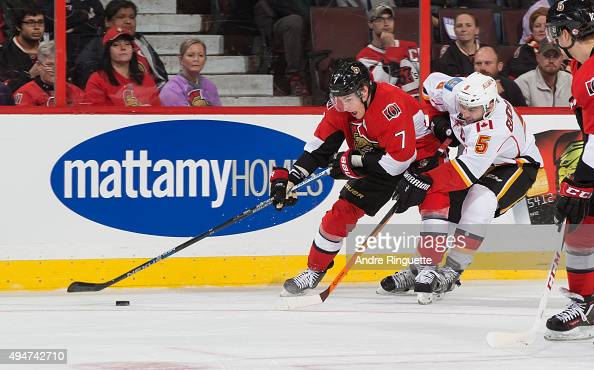 Kyle Turris of the Ottawa Senators fends off Mark Giordano of the Calgary Flames as he stickhandles the puck along the boards at Canadian Tire Centre...