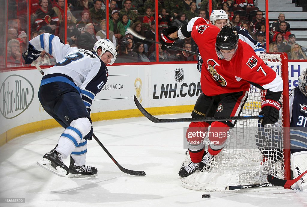 Kyle Turris #7 of the Ottawa Senators gets bumped into the net as he tries to control the puck against Jacob Trouba #8 of the Winnipeg Jets at Canadian Tire Centre on November 8, 2014 in Ottawa, Ontario, Canada.