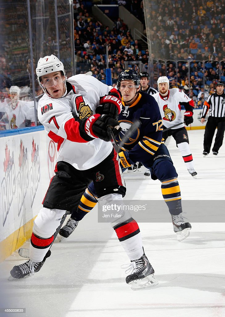 Kyle Turris of the Ottawa Senators passes the puck along the boards as Luke Adam of the Buffalo Sabres follows the play at First Niagara Center on...