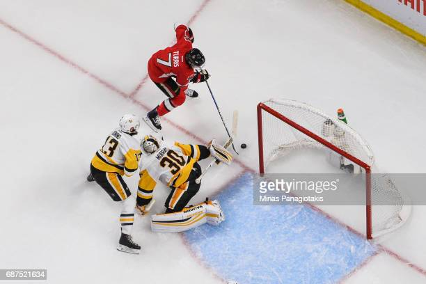 Kyle Turris of the Ottawa Senators tries to get the puck past goaltender Matt Murray while Nick Bonino of the Pittsburgh Penguins defends in Game Six...