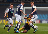 Kyle Vassell of Shrewsbury Town is tackled by Shaun Williams and Chris Taylor of Millwall during the Sky Bet League One match between Millwall and...