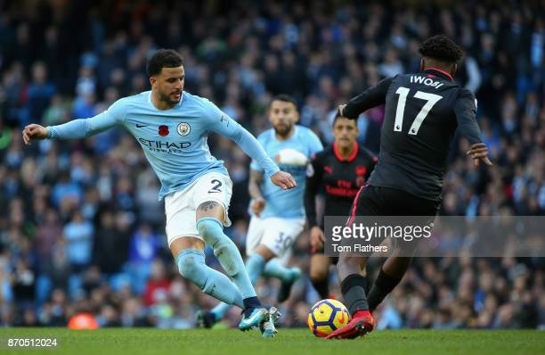 Kyle Walker of Manchester City and Alex Iwobi of Arsenal battle for possession during the Premier League match between Manchester City and Arsenal at...