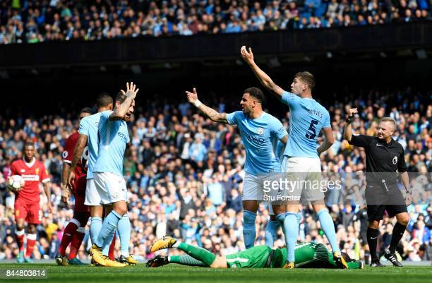 Kyle Walker of Manchester City and John Stones of Manchester City gesture for the Manchester City medical team as Ederson of Manchester City goes...