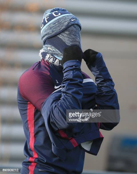 Kyle Walker struggles to get his scarf on during training at Manchester City Football Academy on December 12 2017 in Manchester England