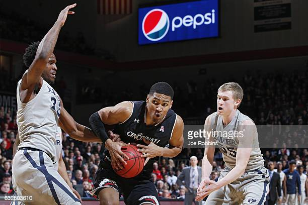 Kyle Washington of the Cincinnati Bearcats goes to the basket against JP Macura and RaShid Gaston of the Xavier Musketeers in the second half of the...