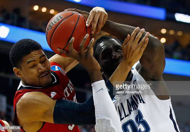 Kyle Washington of the North Carolina State Wolfpack and Daniel Ochefu of the Villanova Wildcats go after the ball in the first half during the third...