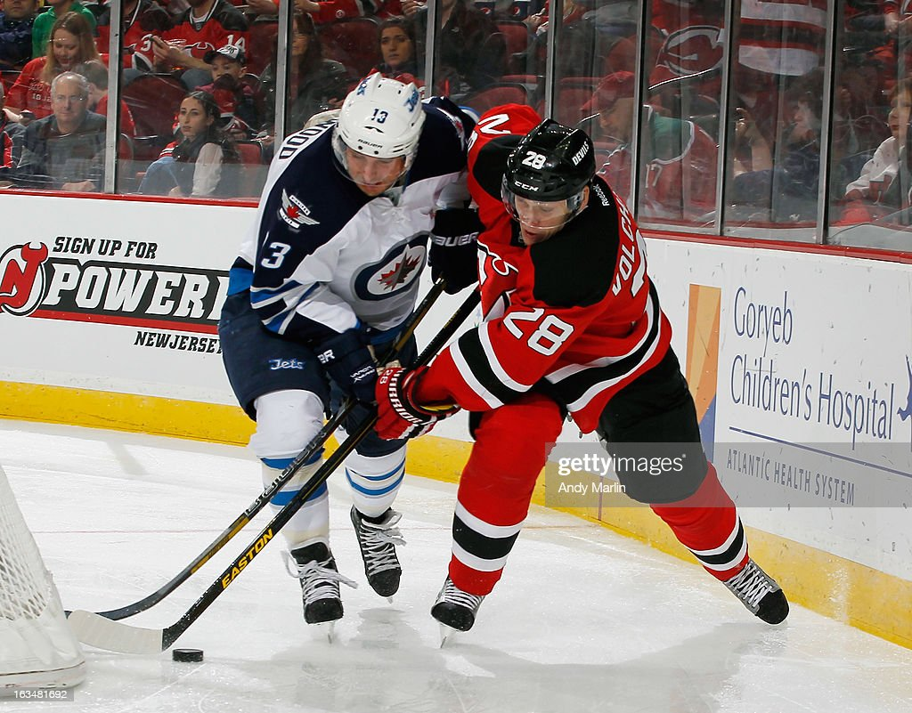 Kyle Wellwood #13 of the Winnipeg Jets and Anton Volchenkov #28 of the New Jersey Devils battle for control of the puck during the game at the Prudential Center on March 10, 2013 in Newark, New Jersey.