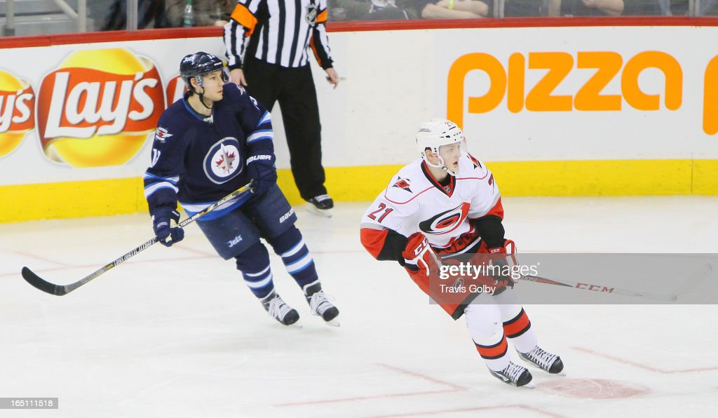 <a gi-track='captionPersonalityLinkClicked' href=/galleries/search?phrase=Kyle+Wellwood&family=editorial&specificpeople=577984 ng-click='$event.stopPropagation()'>Kyle Wellwood</a> #13 of the Winnipeg Jets and <a gi-track='captionPersonalityLinkClicked' href=/galleries/search?phrase=Drayson+Bowman&family=editorial&specificpeople=4111563 ng-click='$event.stopPropagation()'>Drayson Bowman</a> #21 of the Carolina Hurricanes keep an eye on the play during third period action at the MTS Centre on March 30, 2013 in Winnipeg, Manitoba, Canada.
