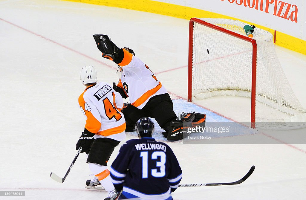 Kyle Wellwood #13 of the Winnipeg Jets and Kimmo Timonen #44 of the Philadelphia Flyers watch as the puck flies over the glove of goaltender Ilya Bryzgalov #30 for a third period goal at the MTS Centre on February 21, 2012 in Winnipeg, Manitoba, Canada.