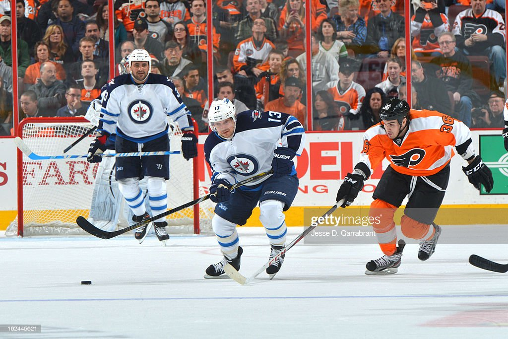 <a gi-track='captionPersonalityLinkClicked' href=/galleries/search?phrase=Kyle+Wellwood&family=editorial&specificpeople=577984 ng-click='$event.stopPropagation()'>Kyle Wellwood</a> #13 of the Winnipeg Jets chases the puck against Zac Rinaldo #36 of the Philadelphia Flyers on February 23, 2013 at the Wells Fargo Center in Philadelphia, Pennsylvania.