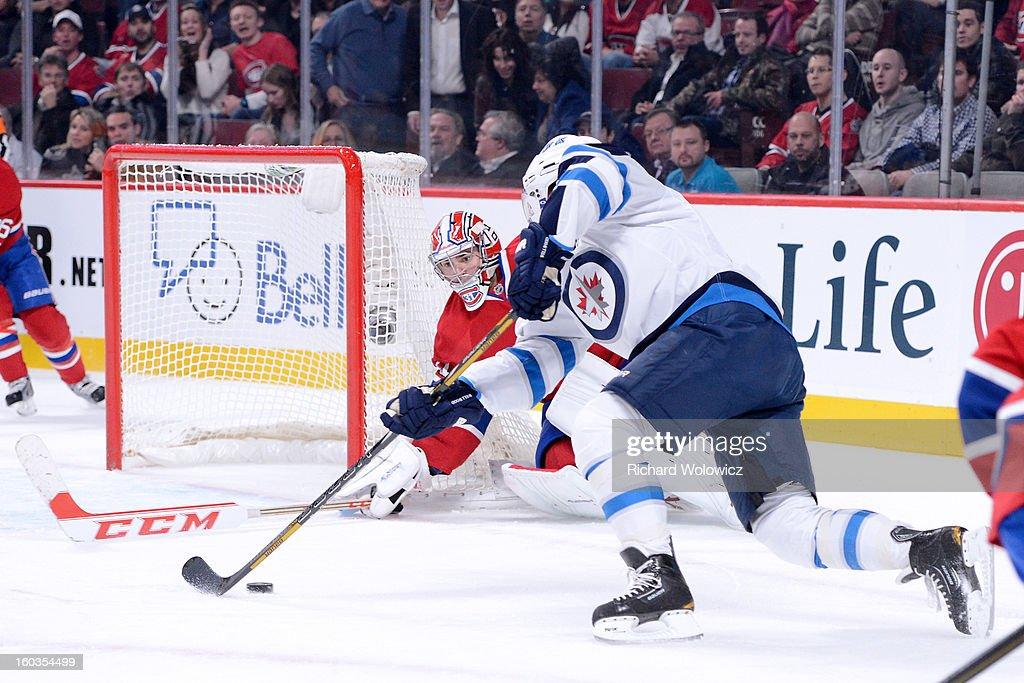 <a gi-track='captionPersonalityLinkClicked' href=/galleries/search?phrase=Kyle+Wellwood&family=editorial&specificpeople=577984 ng-click='$event.stopPropagation()'>Kyle Wellwood</a> #13 of the Winnipeg Jets misses an empty net attempt after <a gi-track='captionPersonalityLinkClicked' href=/galleries/search?phrase=Carey+Price&family=editorial&specificpeople=2222083 ng-click='$event.stopPropagation()'>Carey Price</a> #31 of the Montreal Canadiens was caught out of his goal during the NHL game at the Bell Centre on January 29, 2013 in Montreal, Quebec, Canada. The Canadiens defeated the Jets 4-3.