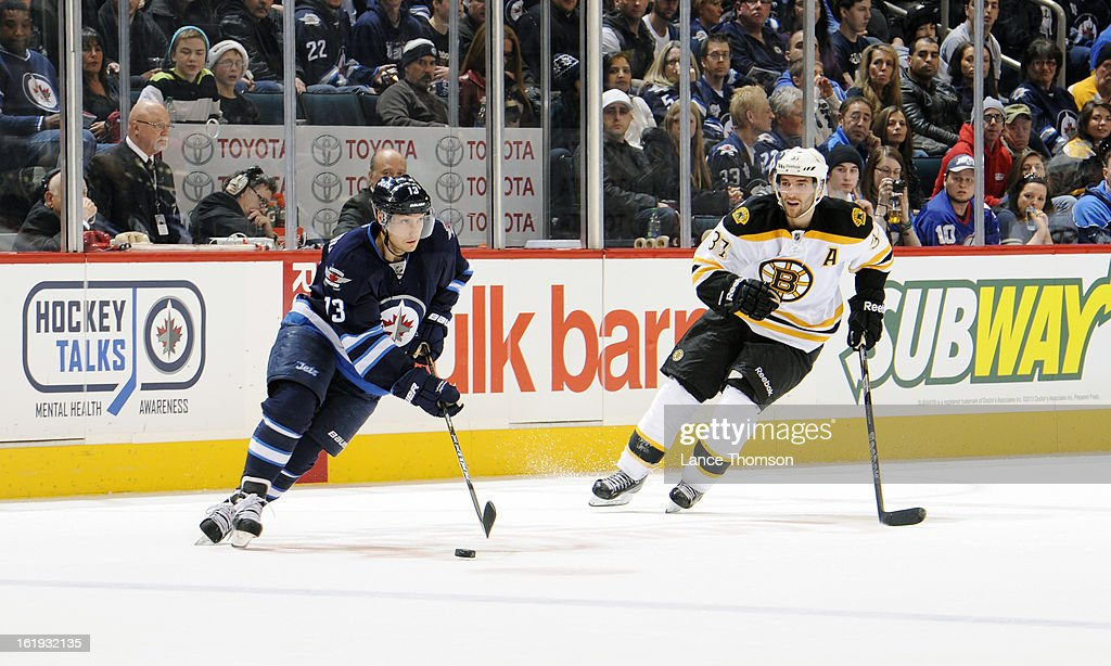 Kyle Wellwood #13 of the Winnipeg Jets plays the puck as Patrice Bergeron #37 of the Boston Bruins gives chase during third period action at the MTS Centre on February 17, 2013 in Winnipeg, Manitoba, Canada.