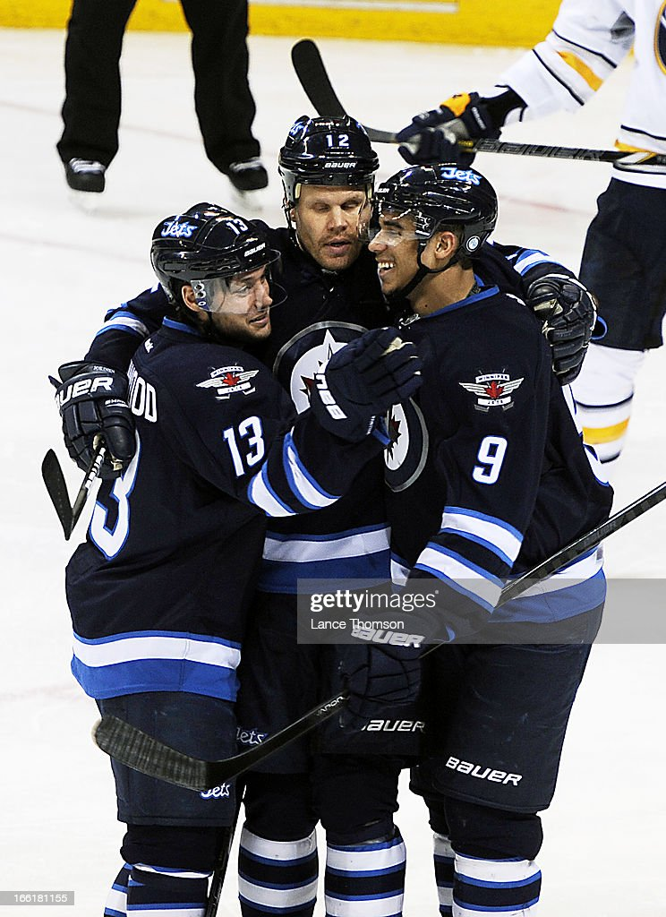 Kyle Wellwood #13, Olli Jokinen #12 and Evander Kane #9 of the Winnipeg Jets celebrate a second period goal against the Buffalo Sabres at the MTS Centre on April 9, 2013 in Winnipeg, Manitoba, Canada.