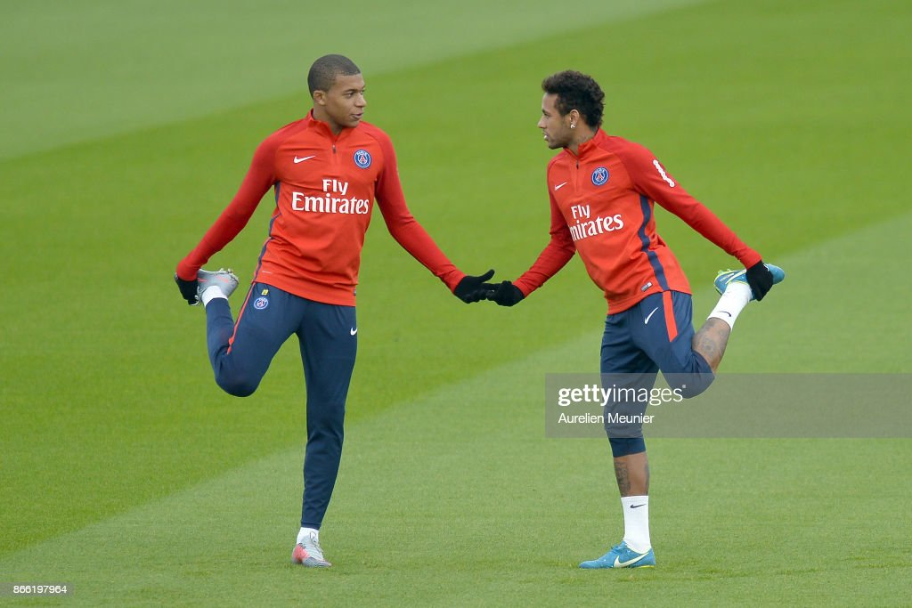 Kylian Mbappe (L) and Neymar Jr of Paris Saint-Germain warm up during a Paris Saint-Germain practice session at Centre Ooredoo on October 25, 2017 in Paris, France.
