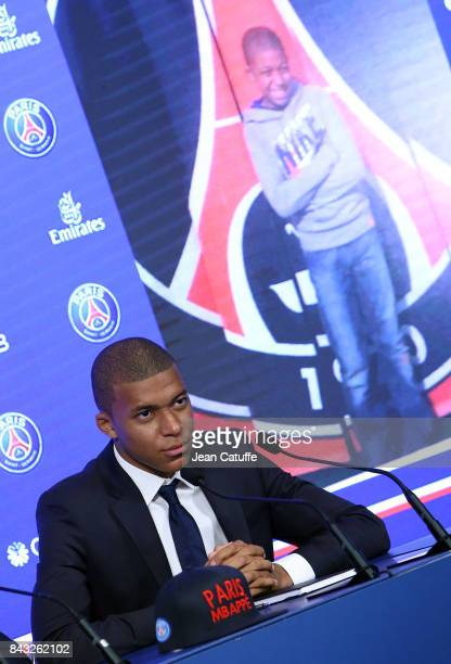 Kylian Mbappe here in front of a picture of him younger posing at Parc des Princes is presented as new player of Paris Saint Germain by President of...