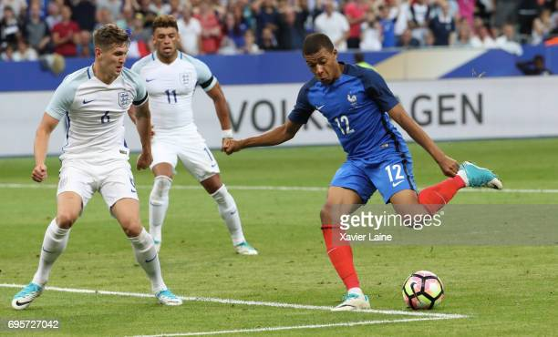 Kylian Mbappe in action with John Stones of England during the International Friendly match between France and England at Stade de France on June 13...