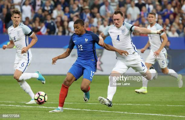 Kylian Mbappe in action with Philip Jones of England during the International Friendly match between France and England at Stade de France on June 13...