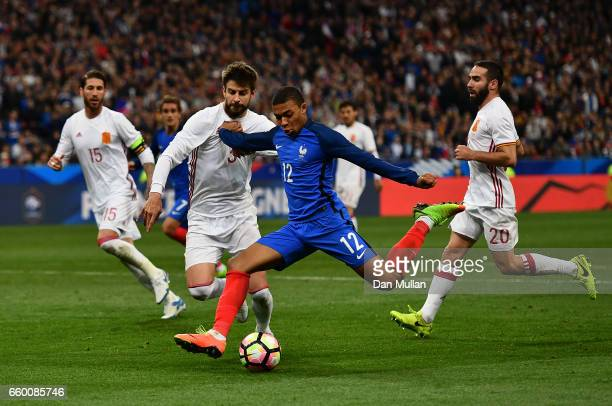 Kylian Mbappe of France holds off Gerard Pique of Spain to take a shot at goal during the International Friendly match between France and Spain at...