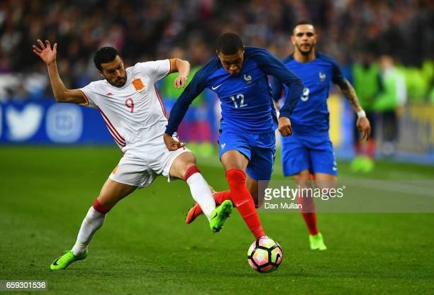 Kylian Mbappe of France is tackled by Pedro of Spain during the International Friendly match between France and Spain at Stade de France on March 28...