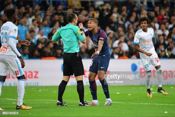Kylian Mbappe of PSG appeals to referee Ruddy Buquet for a penalty and receives a yellow card for his troubles during the Ligue 1 match between...