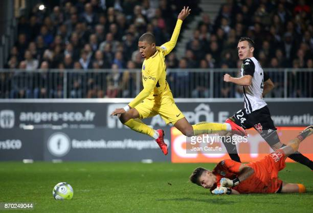 Kylian Mbappe of PSG passes by goalkeeper of Angers Mathieu Michel and Romain Thomas to score his second goal the fifth for PSG during the French...