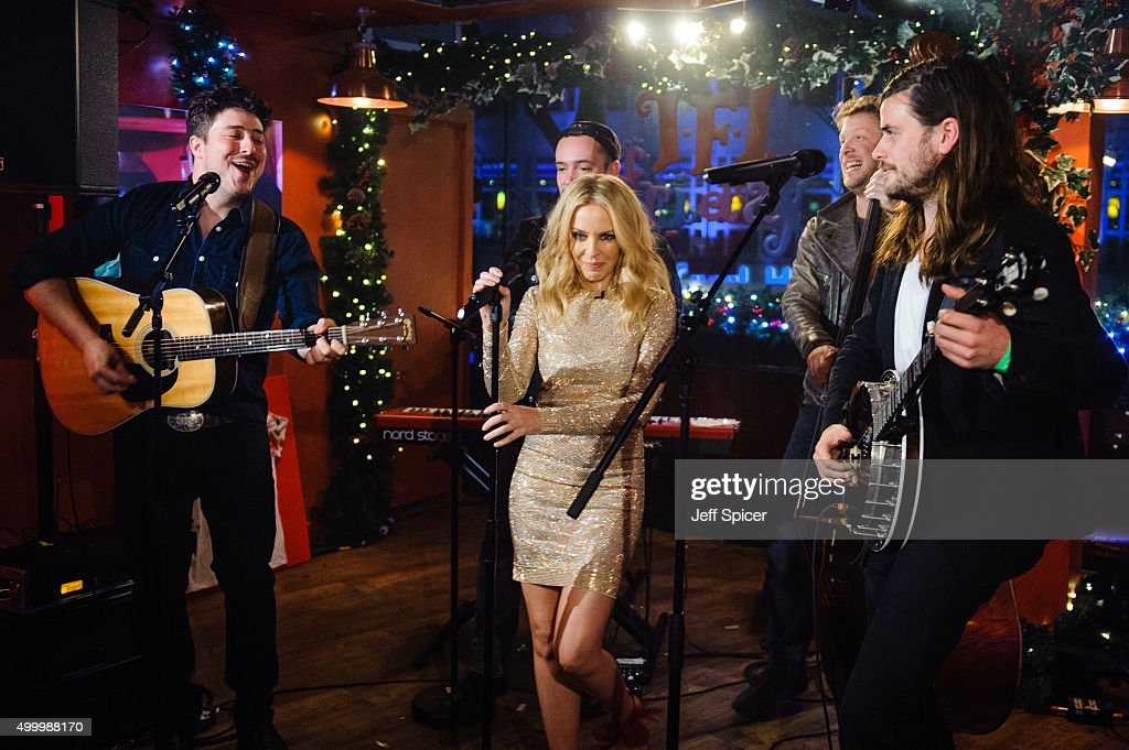 Kylie Minogue with Marcus Mumford Ted Dwane and Winston Marshall from Mumford and Sons perform during a live broadcast of 'TFI Friday' on December 4...