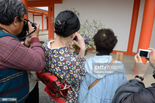 Kyoto Imperial Palace Japanese woman wearing kimono photographs an ikebana at the Kyoto Imperial Palace aka Kyotogosho the former ruling palace of...