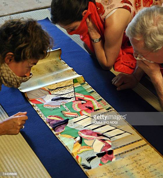 Visiting French journalists look at highquality silk fabrics or Nishijin silk reproductions of the illustrated Tale of Genji handscrolls made by...