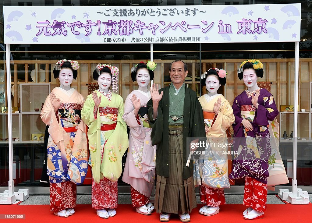 Kyoto Mayor Daisaku Kadokawa (3rd R) and five 'Maiko,' or apprentice geisha, (from L-R) Ichitomi from Gion Kobu, Toshitomo from Miyagawa cho, Chizu from Ponto cho, Ichimari from Kami Shichiken and Tomitae from Gion Higashi, pose in a photo session during their 'We are alive and well, Kyoto' campaign in Tokyo on October 4, 2013. The campaign was held to attract autumn tourists as Kyoto's scenic tourist area of Arashiyama has recovered from the flood disaster caused by Typhoon Man-yi on September 16, 2013.