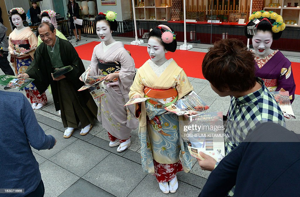 Kyoto Mayor Daisaku Kadokawa (rear 4th L) and five 'Maiko,' or apprentice geisha, (from L-R) Ichitomi from Gion Kobu, Toshitomo from Miyagawa cho, Chizu from Ponto cho, Ichimari from Kami Shichiken and Tomitae from Gion Higashi, hand out Kyoto tourism leaflets to pedestrians during their 'We are alive and well, Kyoto' campaign in Tokyo on October 4, 2013. The campaign was held to attract autumn tourists as Kyoto's scenic tourist area of Arashiyama has recovered from the flood disaster caused by Typhoon Man-yi on September 16, 2013. AFP PHOTO / TOSHIFUMI KITAMURA
