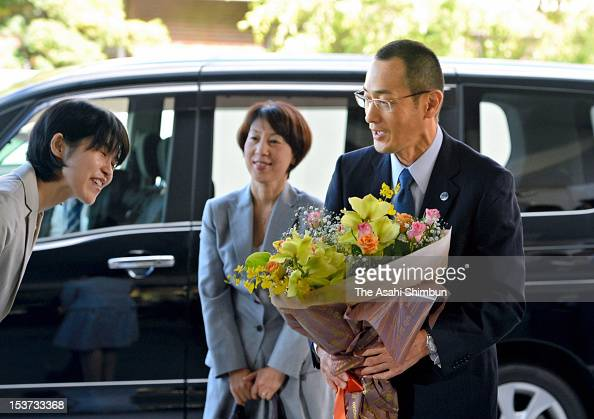 Kyoto University Professor Shinya Yamanaka receives a flower bunch upon arrival at Kyoto University on October 9 2012 in Kyoto Japan Yamanaka and Sir...