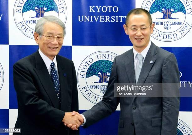 Kyoto University Professor Shinya Yamanaka shakes hands with Kyoto University president Hiroshi Matsumoto during a press conference at Kyoto...