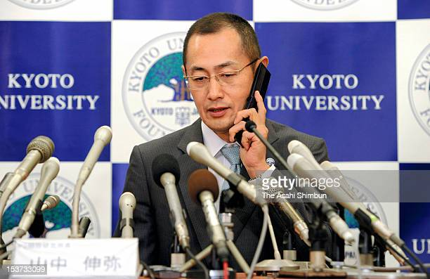 Kyoto University Professor Shinya Yamanaka speaks through the phone with Japanese Prime Minister Yoshihiko Noda during a press conference at Kyoto...