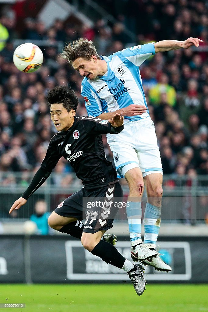 Kyoung Rok Choi (L) of Hamburg and Kai Buelow (R) of Muenchen compete for the ball during the Second Bundesliga match between FC St. Pauli and 1860 Muenchen at Millerntor Stadium on April 29, 2016 in Hamburg, Germany.