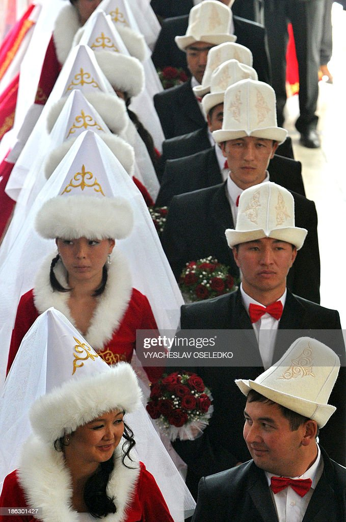 Kyrgyz brides and bridegrooms attend a mass wedding ceremony in the capital Bishkek on October 30, 2013. Fifty couples took part in the mass wedding ceremony sponsored by a state company. AFP PHOTO / VYACHESLAV OSELEDKO
