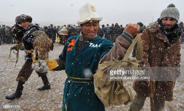 A Kyrgyz hunter carries a golden eagle during the hunting festival 'Salburun' in the village of Bokonbayevo some 300 km outside Kyrgyzstan's capital...