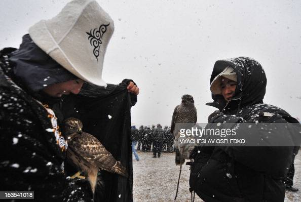 Kyrgyz hunters hold their golden eagles during the hunting festival 'Salburun' in the village of Bokonbayevo some 300 km outside Kyrgyzstan's capital...