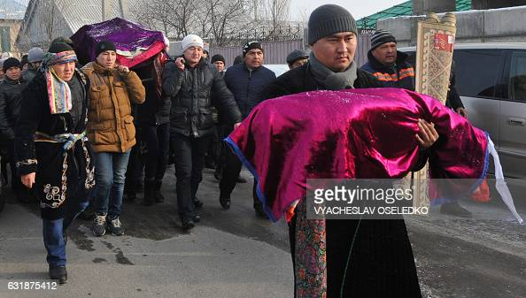 TOPSHOT Kyrgyz men carry the bodies of a family killed the day before in a Turkish cargo plane crash during their funeral in Bishkek on January 17...