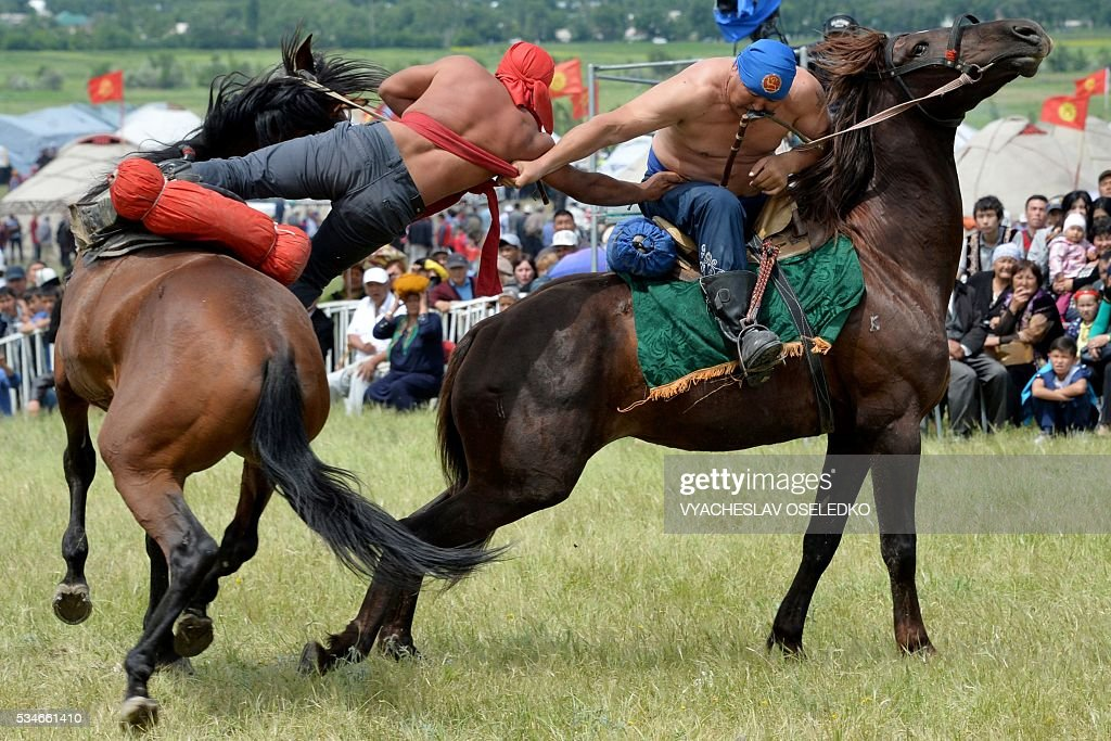 Kyrgyz men on horseback compete during their traditional game of 'Oodarysh' during the celebrations of the 90th anniversary formation of the Chui region in the village of Kuntu some 20 kms from Bishkek on May 27, 2016. / AFP / VYACHESLAV