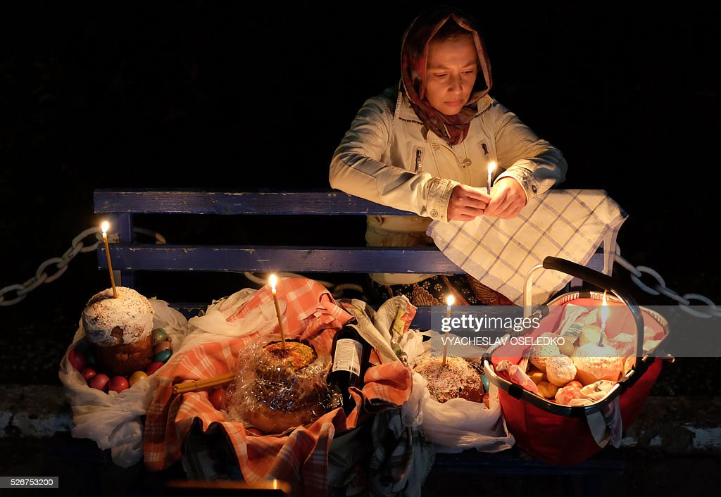 A Kyrgyz Orthodox believer holds a candle as she celebrates Orthodox Easter during a midnight mass at a church in a village outside Bishkek early on May 1, 2016. / AFP / VYACHESLAV