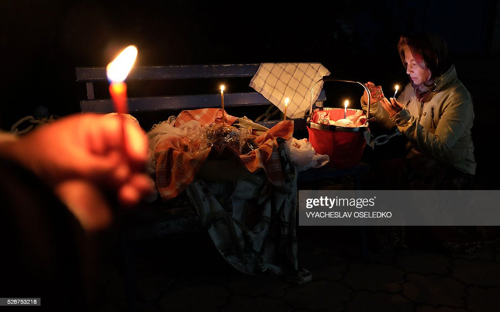 Kyrgyz Orthodox believers hold candles as they celebrate Orthodox Easter during a midnight mass at a church in a village outside Bishkek early on May 1, 2016. / AFP / VYACHESLAV