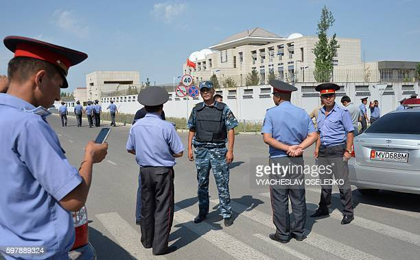 TOPSHOT Kyrgyz police officers gather outside the Chinese embassy in Bishkek on August 30 2016 A van driven by a suicide bomber exploded after...